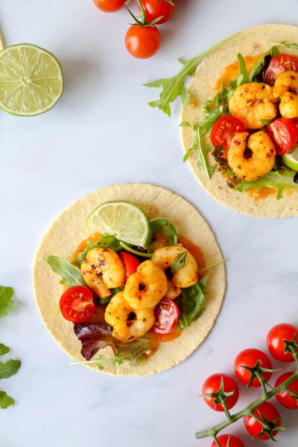 BBQ spicy saffron shrimp tacos served with salad leaves, lime and cherry tomatoes...